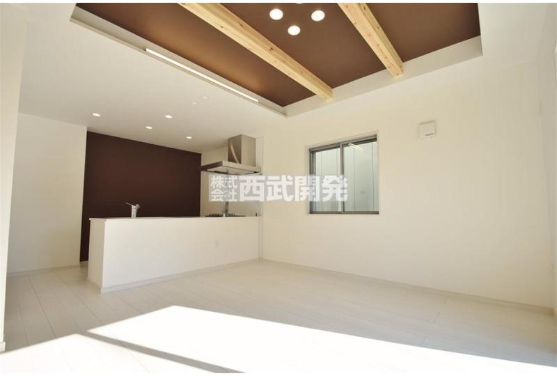 【居間】1号棟 LDKは折上天井となっております。 あえて見せる化粧梁、直下を照らすLED照明がなんともオシャレを演出いたします。タタミコーナーと併せて合計16.97帖の広さがあります。