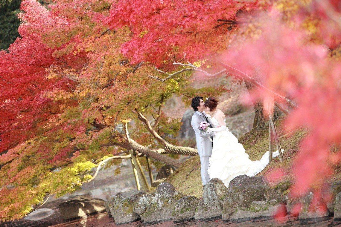Romantic kiss among the autumn leaves— Photo by Kaoru Photography