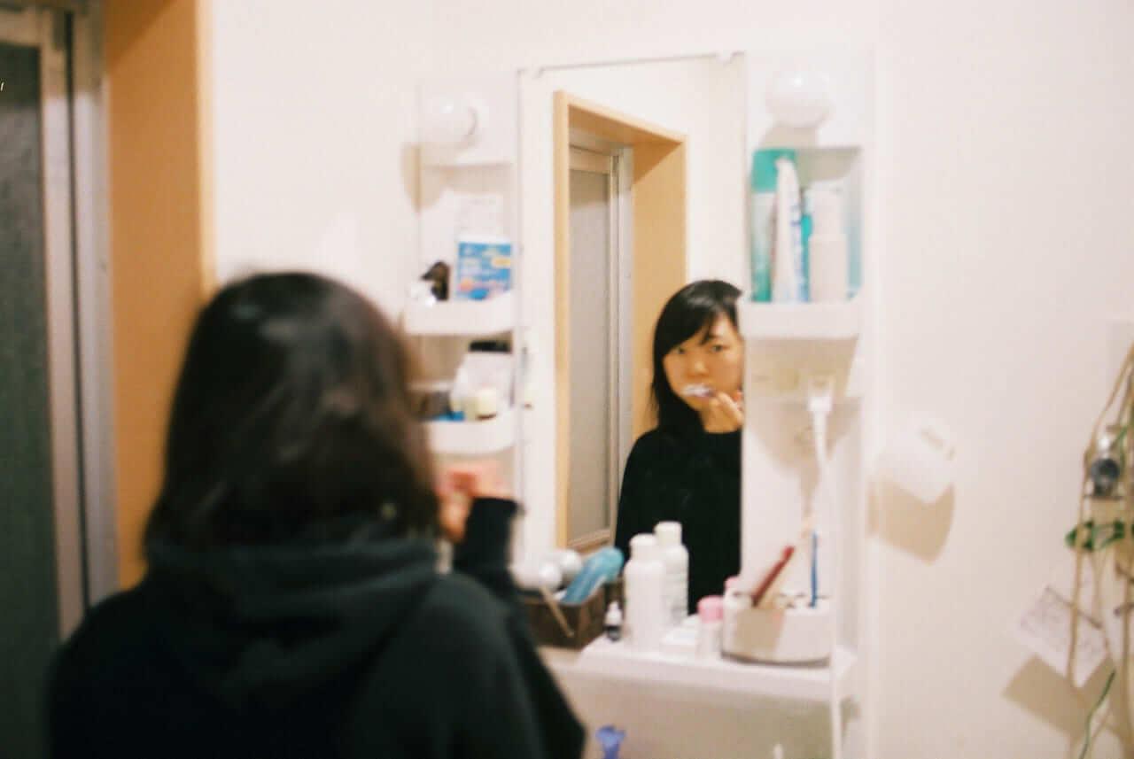 鏡を見ながら舌を磨いていく
