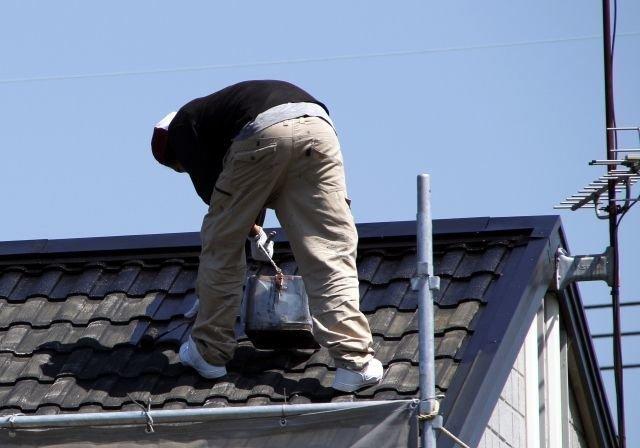 屋根の上で作業する業者