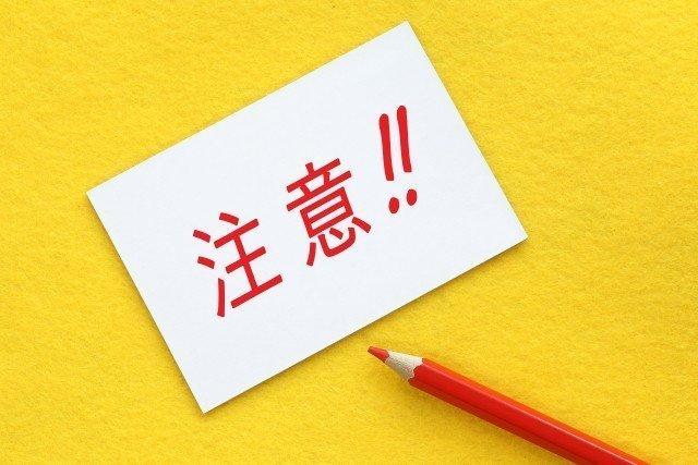 注意と書かれた紙と赤い鉛筆