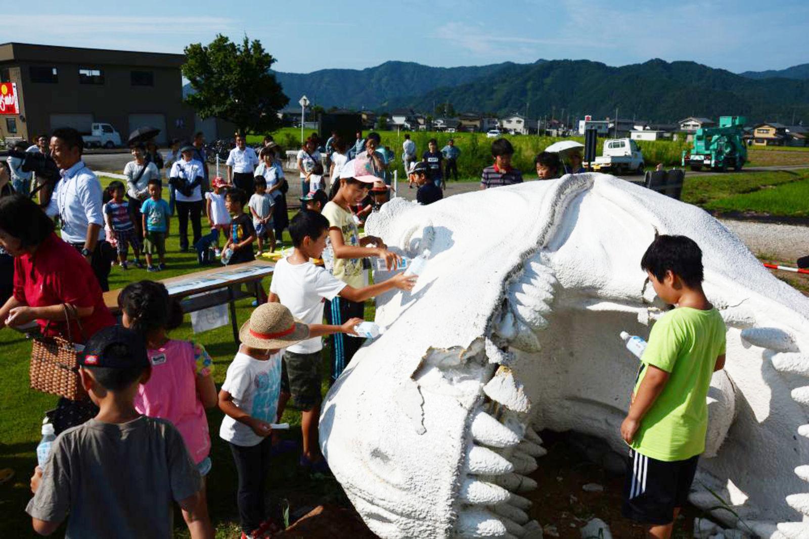 ホワイトザウルスの落ちた頭に、花を手向け水をかけてあげる子どもたち(写真提供: 勝山市)