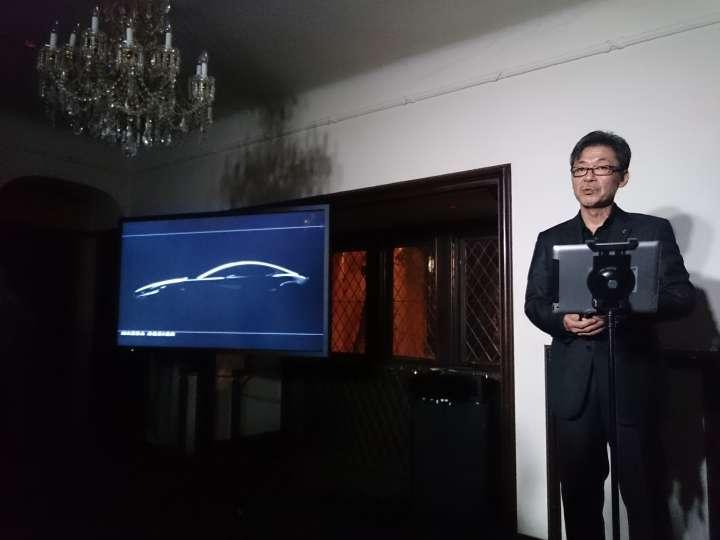 新型ロータリーエンジンを搭載するスポーツクーペをチラ見せするデザイン執行役員の前田育男氏。モニターに映された画像はこれまで発表されていない角度のもの。サービス精神旺盛!