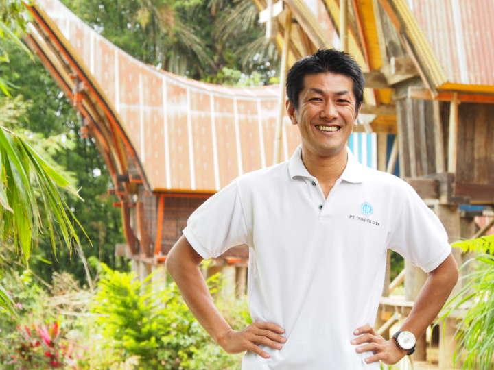 トラジャ在住の吉原聡さん。背景に写っているのはトラジャ族の伝統的な高床式住居「トンコナン」