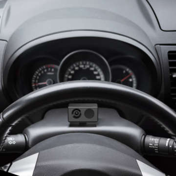 Modern car interior fragment with steering wheel and control panel, driver view point