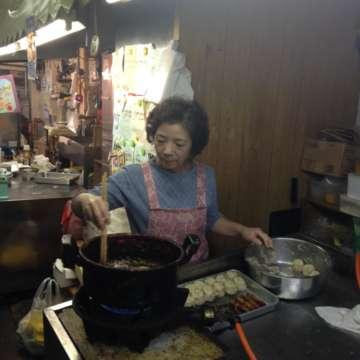 年季の入った鍋でいがめんちを揚げる、スタッフの山田けい子さん