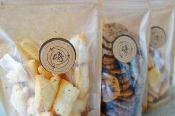 同店限定商品のパッケージに使われる「松崎」のロゴは、かつて使っていた紋をあらためて復刻したもの。揚餅(塩・マヨネーズ・バジル)、「小揚丸(胡麻)」は各378円、「八穀おこげ」「ざらめひとくち煎餅」は各432円と価格も値ごろで、手土産にもオススメだ