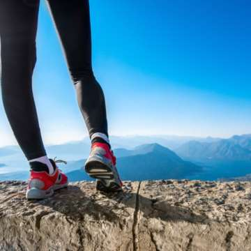 Woman's sporty legs in sneakers on the mountain hill