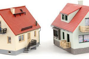 Models of two houses on white background. Close-up.