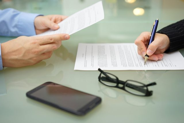 businessman and woman are reading and signing contract