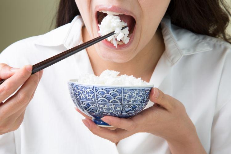アミラーゼを持つ白米を食べる女性