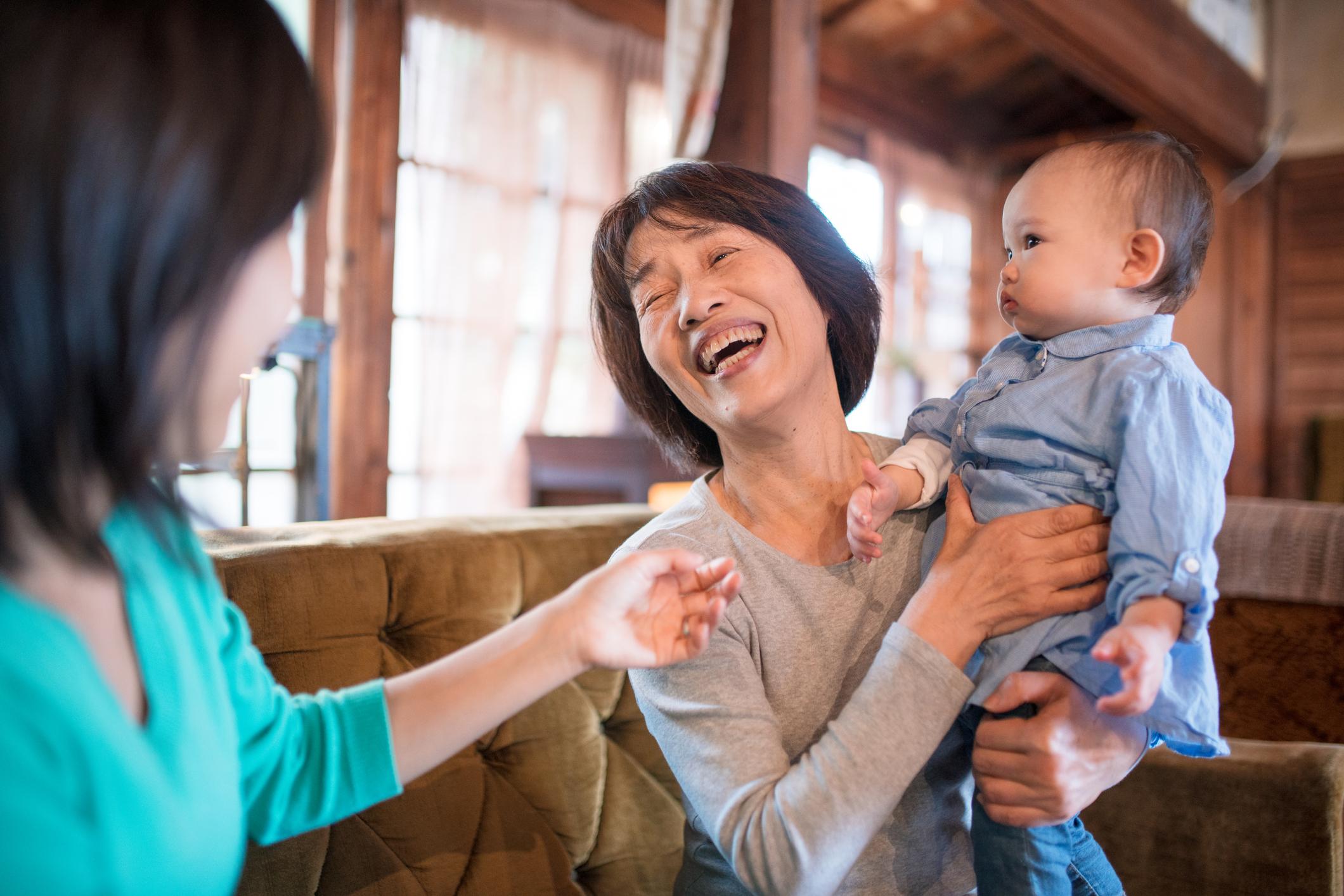 年配の女性に抱っこされる赤子