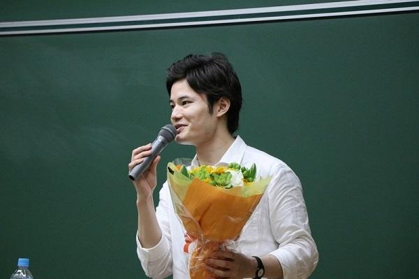 学生さんからもらった花束を手にするてぃ先生
