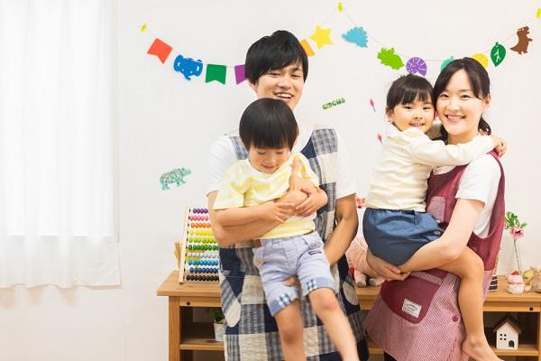 子どもを抱っこしている若い男性と女性
