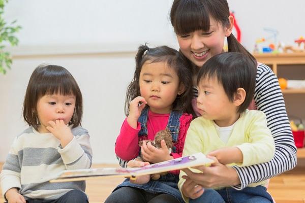 子どもたちに絵本を読んでいる保育士の女性