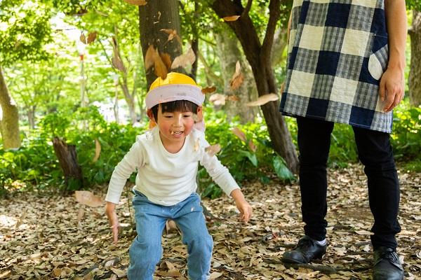 落ち葉で遊ぶ男の子