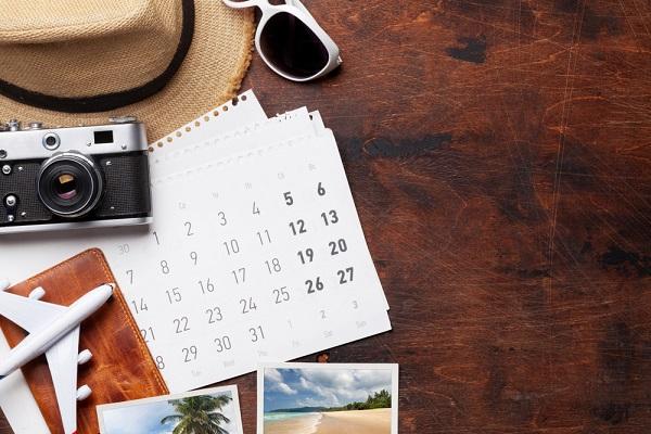 カレンダー、飛行機やカメラなどが旅行を連想させる写真