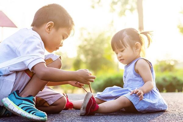 男の子が女の子の靴紐を結んでいる様子