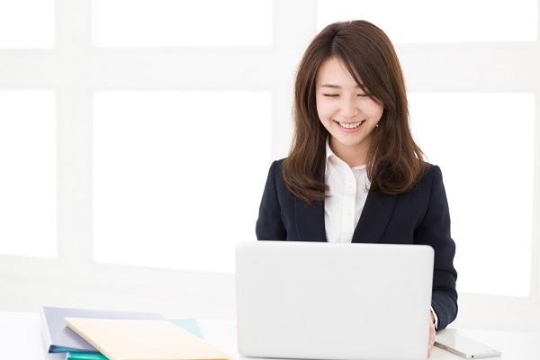 パソコンで作業する笑顔の女性