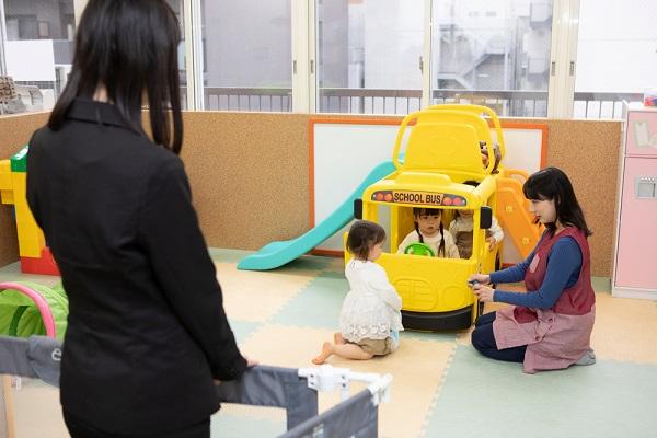 子どもを見ているスーツの女性