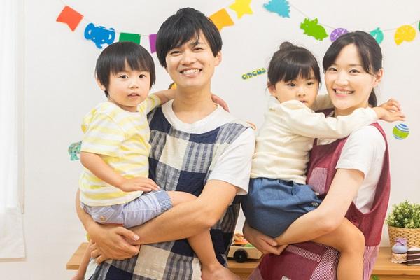 子どもを抱いている保育士の写真