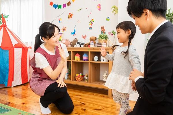 手を振り合っている子どもと保育士の写真