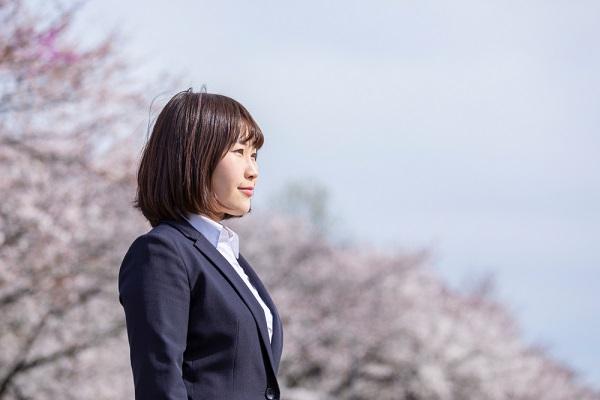 リクルートスーツを着て桜の木の下に立つ女性の写真