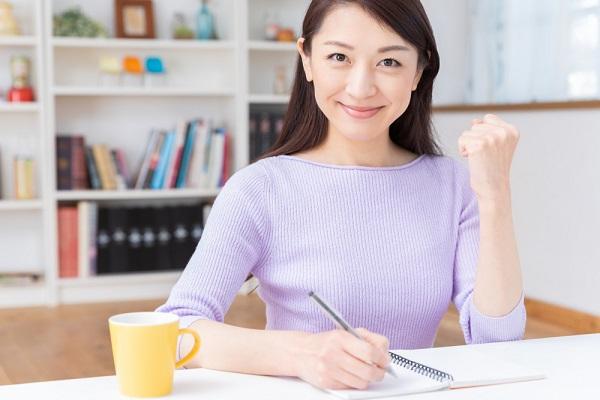 書類を書きながらガッツポーズをしている女性の写真
