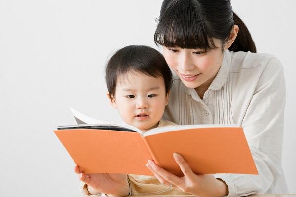 子どもに絵本を読んでいる女性