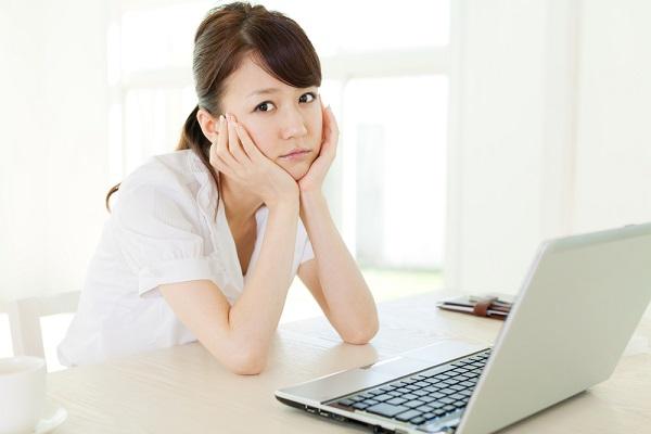 パソコンを前にして困っている女性
