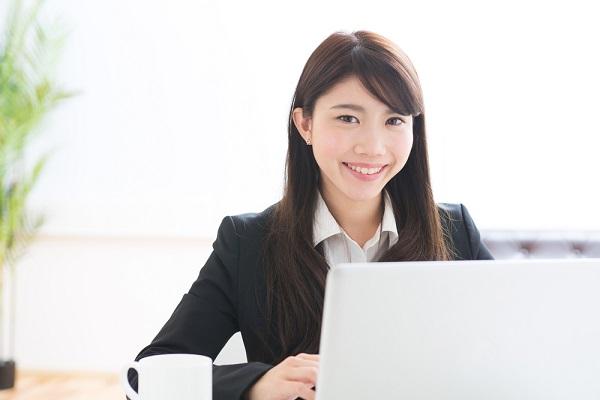パソコンの前で笑顔の女性