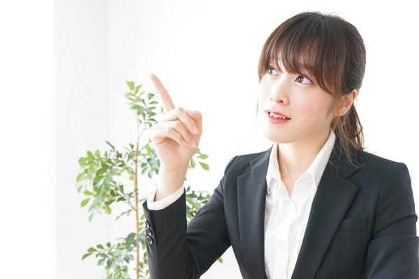 指をさしているスーツの女性