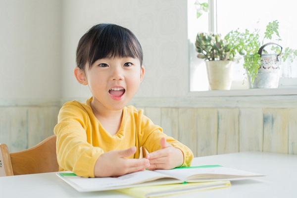 絵本を見て笑う女の子の写真