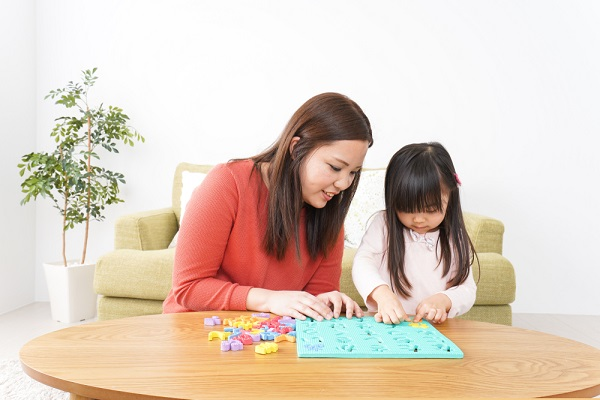 小さな女の子と遊んでいる女性