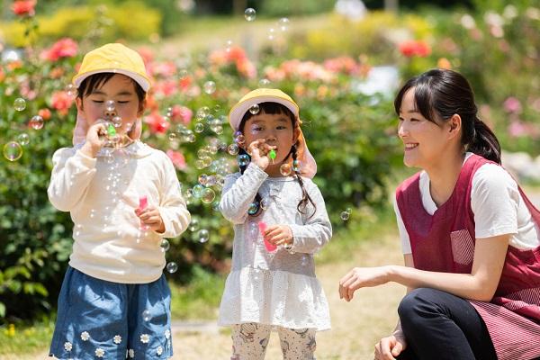シャボン玉で遊ぶ女の子と保育士の写真