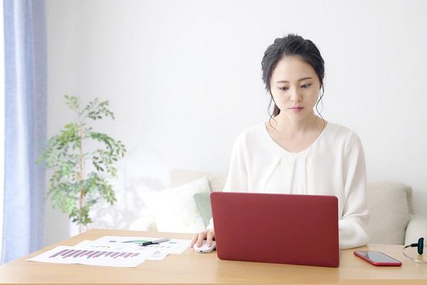 パソコンを見て考えている女性の写真