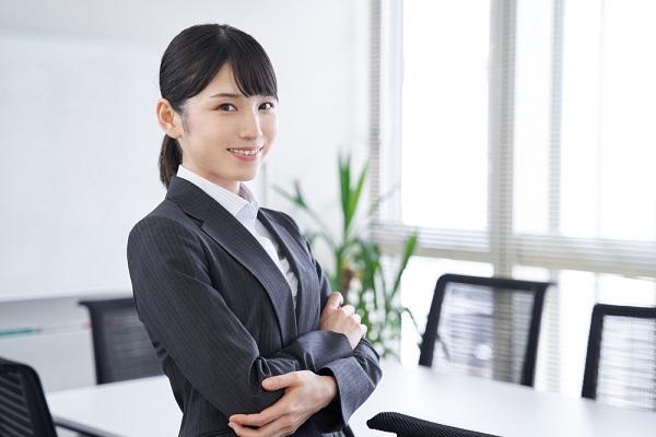 腕を組んでいるスーツの女性