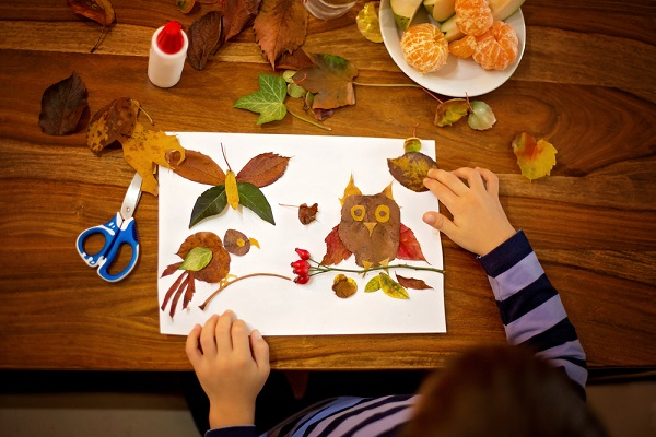 落ち葉で工作を楽しむ子どもの写真