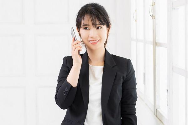 スーツ姿で電話をしている女性