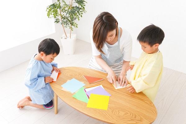 折り紙を折っている保育士と子ども