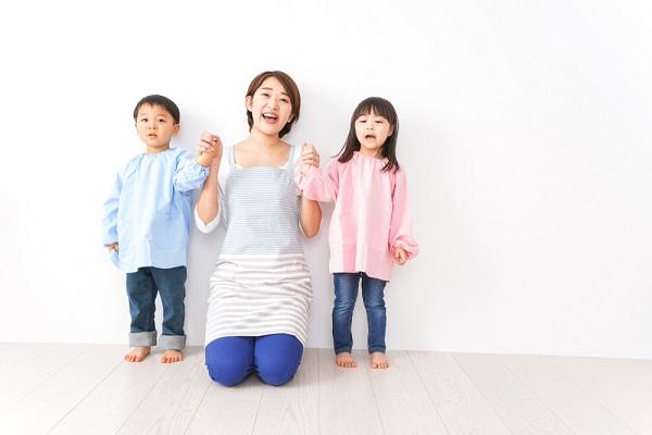 保育士と手をつなぐ子ども