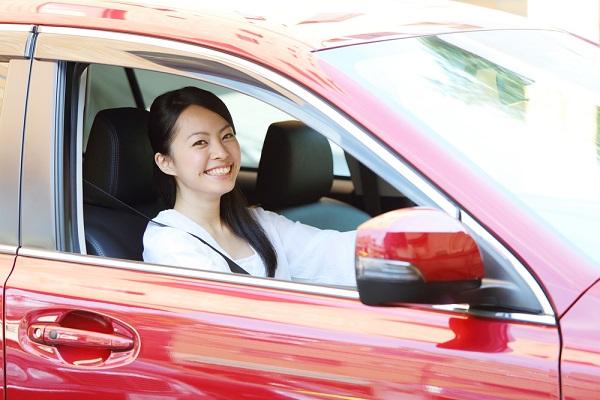 赤い車に乗っている女性