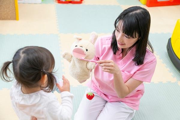 パペットを使って子どもに教える保育士さん