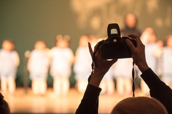 カメラで発表会の様子を撮っている