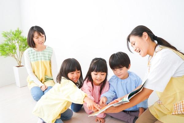 絵本を読む子どもと保育士