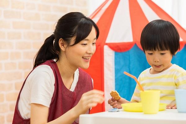 先生とおやつを食べる子ども