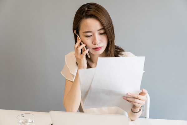 紙を見ながら電話する女性