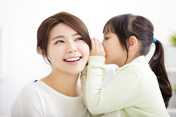 内緒でお話をする保育士と子どもの写真