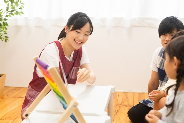 子どもに絵本を見せる先生