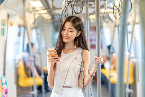 電車内でスマホを見ている女性